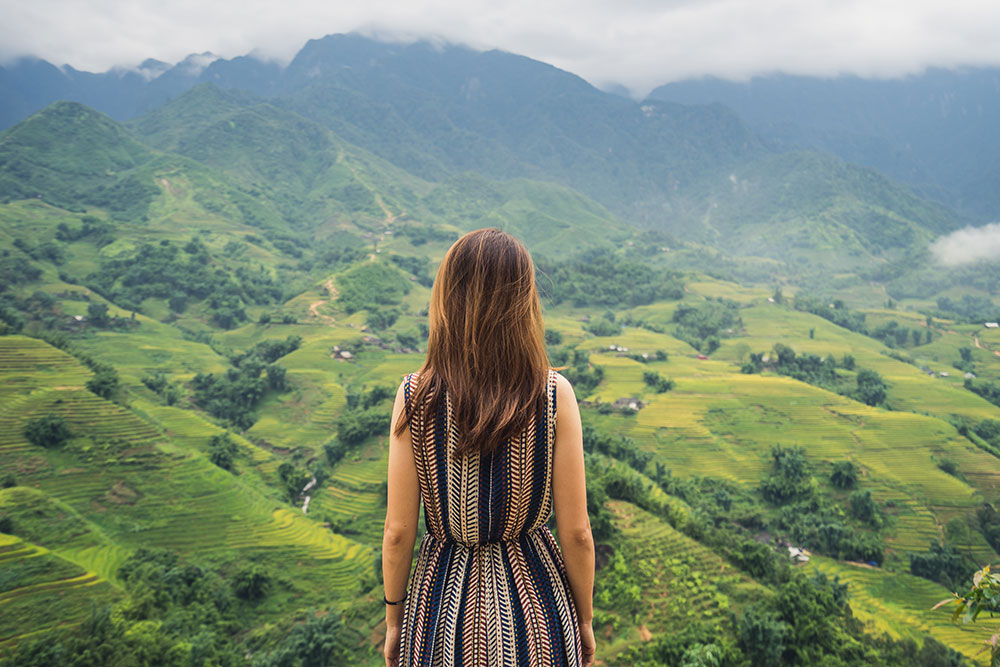 A dark-haired woman looking over luscious, green rice paddies in Vietnam
