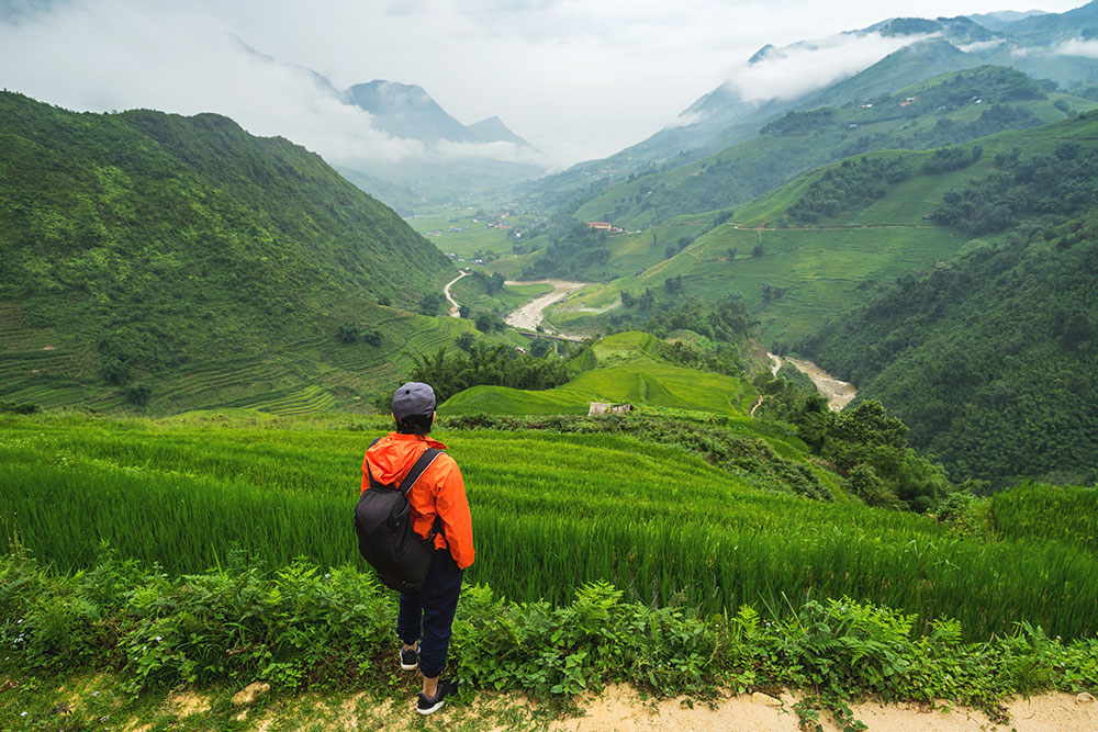 Sapa Trekking in Northern Vietnam – A traveller looking down over a green, mountainous valley.