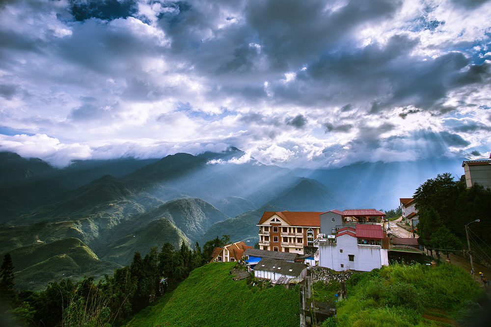 Sapa trekking in Northern Vietnam – Large buildings perched on a green mountain, illuminated by sunlight shining through the clouds.