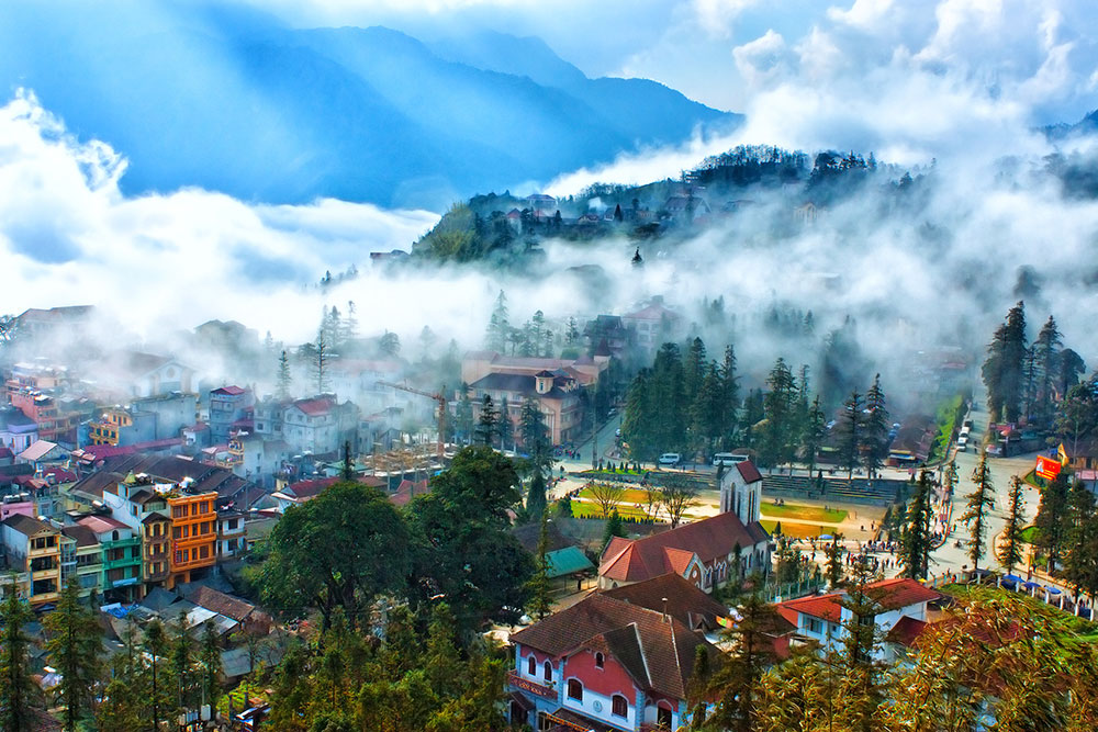 Sapa trekking in Northern Vietnam – A lively town, with trees in the foreground and buildings in the background.